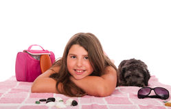 Girl in swimsuit at the beach with dog. Smiling brunette teenage girl in swimsuit at the beach with her shipoo dog (studio setting with beach and personal items Royalty Free Stock Image