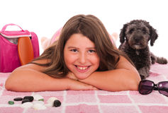 Girl in swimsuit at the beach with dog. Smiling brunette teenage girl in swimsuit at the beach with her shipoo dog (studio setting with beach and personal items Royalty Free Stock Photos