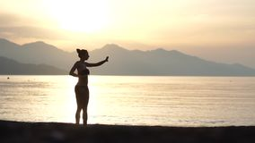 A girl in a swimsuit does exercises on the seashore in the morning at sunrise. Shooting in slow motion stock video