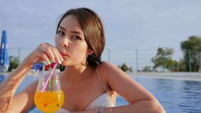 Girl drink colorful cocktail and giving thumbs up at Poolside on background sky in Summer vacation. Girl in swimsuit drink colorful cocktail and giving thumbs up stock video footage
