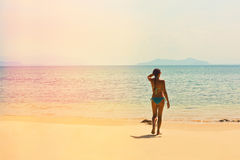 Girl in a swimsuit on the empty tropical beach Stock Image