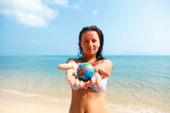 Small globe on the extended hands at girl. A girl in a swimsuit holds a globe in her arms, stretched forward, against the background of the Pacific Ocean royalty free stock photos
