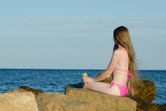 Girl in swimsuit with ice cream in her hand talking on the phone on the rocks near the sea Stock Photography