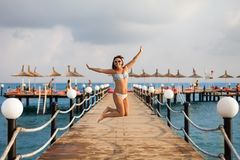 The girl in the swimsuit jumped on the pier. Happy girl on the pier. Freedom concept. The charming girl jumpping on the pier. stock images