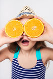 Girl in swimsuit making fake eyeglasses with oranges. Llittle girl in swimsuit and summer hat having fun with half oranges making fake eyeglasses with expression Royalty Free Stock Image