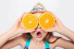 Girl in swimsuit making fake eyeglasses with oranges. Llittle girl in swimsuit and summer hat having fun with half oranges making fake eyeglasses with expression Royalty Free Stock Photos