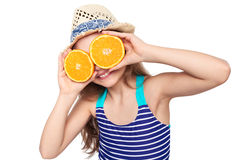 Girl in swimsuit making fake eyeglasses with oranges. Llittle girl in swimsuit and summer hat having fun with half oranges making fake eyeglasses, over white Stock Photography