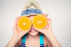 Girl in swimsuit making fake eyeglasses with oranges. Llittle girl in swimsuit and summer hat having fun with half oranges making fake eyeglasses, toned image Stock Photography