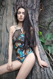 Girl in swimsuit near tree stock images