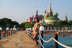Girl in a swimsuit on the pier on the background of the hotel. girl posing on the wooden pier on the beach, against the backdrop. Of a luxury hotel stock image