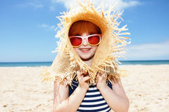 Girl in swimsuit playing with big straw hat on white beach Royalty Free Stock Image