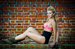 Girl in swimsuit posing provocatively in front of a brick wall Royalty Free Stock Photography
