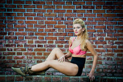 Girl in swimsuit posing provocatively in front of a brick wall Stock Images