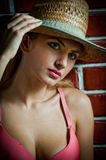Girl in swimsuit posing provocatively in front of a brick wall Royalty Free Stock Photo