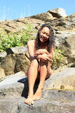 Girl in swimsuit on rock. Tropical girl - smiling woman with long black hair in swimsuit sitting on rock Royalty Free Stock Photo
