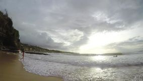 Girl in a swimsuit runs along the beach at sunset in slow motion, Bali stock video footage