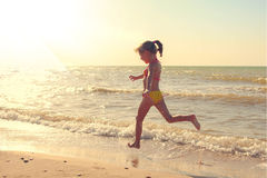 Girl in swimsuit runs along the shore of the sea. Toned image Stock Image