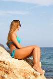 Girl in swimsuit sea sitting on the big stone Royalty Free Stock Photos