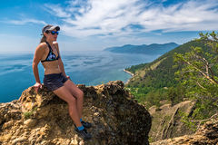 Girl in swimsuit sits on a cliff-top Skriper Stock Photo