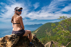 Girl in swimsuit sits on a cliff-top Skriper Royalty Free Stock Photography