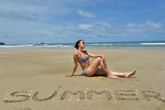 A girl in a swimsuit sits on a deserted sandy beach. Next to the inscription summer on the sand Stock Image