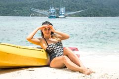Girl on the beach with a canoe royalty free stock photo