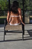 Girl in a swimsuit sitting on a longe chair Royalty Free Stock Image