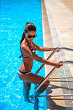 Girl in swimsuit standing on the pool ladder Stock Photos