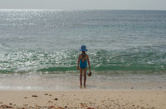 Girl in a swimsuit stands and looks at the ocean Royalty Free Stock Image