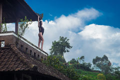 Girl in swimsuit stay on the roof in the mystical abandoned rotten hotel in Bali with blue sky. Indonesia. With blue sky Royalty Free Stock Images