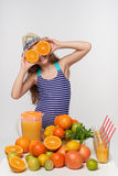 Girl in swimsuit and summer hat with a lot of citrus fruits and orange juice Royalty Free Stock Images