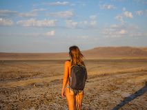 A girl in a swimsuit is walking at sunset over a dry salt lake stock image