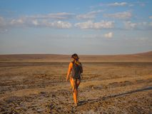 A girl in a swimsuit is walking at sunset over a dry salt lake stock images