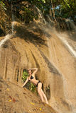 Girl in swimsuit on waterfall Stock Image