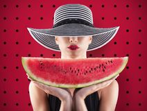 Girl in swimsuit with watermelon in hand and red background. Girl in swimsuit with fresh watermelon in hand and red background royalty free stock photos