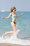 Girl in swimwear and sunglasses running along seashore arms outs Stock Photo