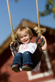 Girl on swing. Girl laughing and smiling on swing in front of barn Royalty Free Stock Image
