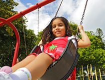 Girl on a Swing. Girl Swinging on a red swing. Shot near feet Royalty Free Stock Photo