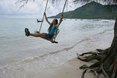 Girl on the swing. Young girl swinging on the beach Royalty Free Stock Photo