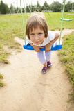Girl and swing. Girl child (three years old) on a swing in the park Stock Photo