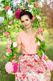 Girl on a swing in flowers in the nature Royalty Free Stock Photography