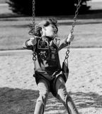 Girl On Swing Having Fun. Little girl on a swing having a really good time singing or yelling while swinging Royalty Free Stock Image