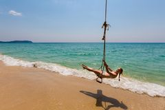 Girl on swing Koh Kood. Summer landscape on tropical koh Kood island  in Thailand. Young sexy girl enjoying swing on Ao Tapao beach Royalty Free Stock Photos