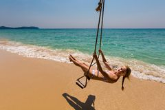 Girl on swing Koh Kood. Summer landscape on tropical koh Kood island  in Thailand. Young sexy girl enjoying swing on Ao Tapao beach Stock Photo