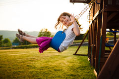 Girl on a swing. Little girl on a swing in a playground Royalty Free Stock Photos