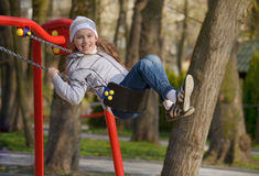 Girl on a swing. One funny girl swinging on a swing hanging Royalty Free Stock Photo