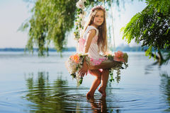 Girl on swing over river. Girl on home made tree swing over river. Swing decorated with flowers. Smiling girl turned around sitting on swing. Girl with flower Royalty Free Stock Photography