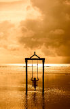 A girl on a swing over the sea at sunset in bali,indonesia 3 Stock Photo