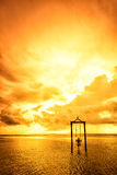 A girl on a swing over the sea at sunset in bali,indonesia 5 Royalty Free Stock Images
