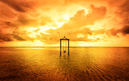 A girl on a swing over the sea at sunset in bali,indonesia 6 Stock Photos